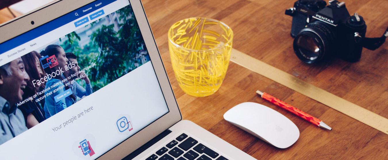 Bild eines Schreibtischs mit Laptops mit Facebook Ads Anzeige